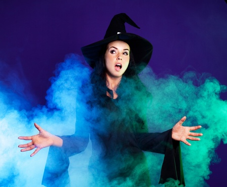 angry brunette witch saying the spell with clouds of smoke around her, isolated against white background Stock Photo
