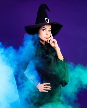 thoughtful young brunette witch with a broom and foam around her, isolated against white background photo