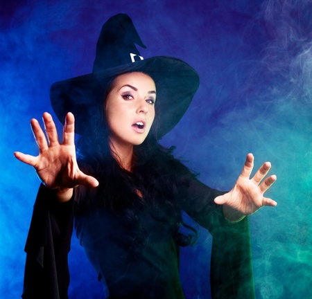 angry brunette witch saying the spell and stretchign her hands to us, with clouds of smoke around her, isolated against white background photo