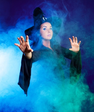 brunette witch saying the spell and stretching her hands to us, with clouds of smoke around her, isolated against white background photo