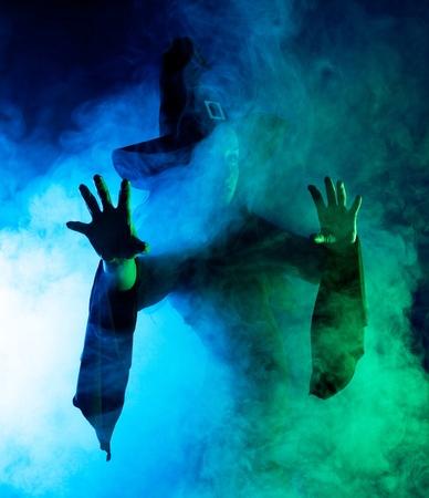 brujas sexis: silueta de una bruja misteriosa diciendo el hechizo y estirando sus manos, con nubes de humo a su alrededor, aislaron sobre fondo blanco