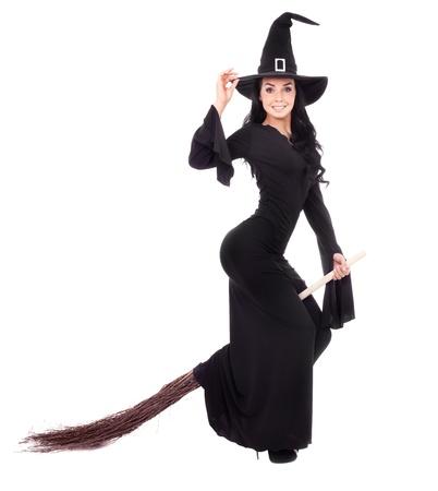 brujas sexis: bastante joven bruja morena con una escoba, aislada sobre fondo blanco Foto de archivo