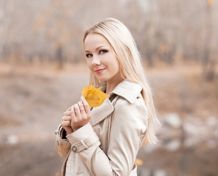 blonde teenager: beautiful young blond woman spending time in the autumn park   Stock Photo