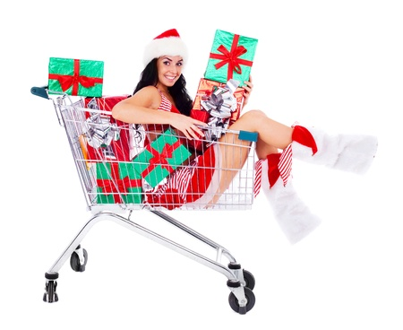 beautiful young brunette woman dressed as Santa sitting in the shopping cart with presents, isolated against white background photo