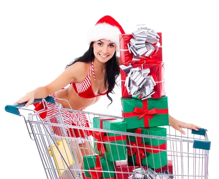 beautiful young brunette woman dressed as Santa with the the shopping cart with a lot of presents, isolated against white background photo