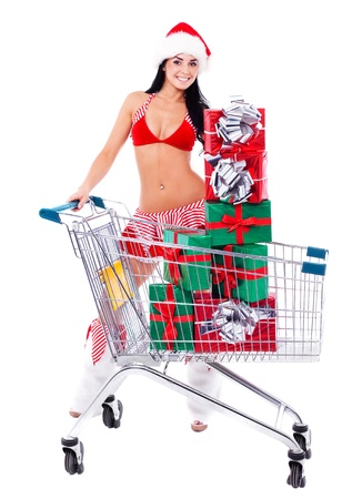 woman shopping cart: beautiful young brunette woman dressed as Santa with the the shopping cart with a lot of presents, isolated against white background Stock Photo