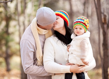 happy young family with their daughter spending time outdoor in the autumn park (focus on the baby) photo