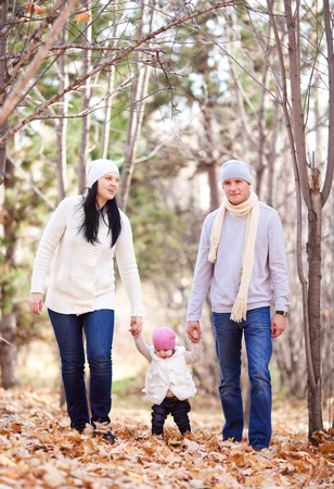 outsides: happy young family with their daughter spending time outdoor in the autumn park (focus on the man and woman)