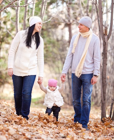 outsides: happy young family with their daughter spending time outdoor in the autumn park