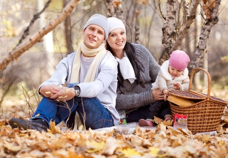 happy young family with their daughter spending time outdoor in the autumn park (focus on the man) Stock Photo - 10944996