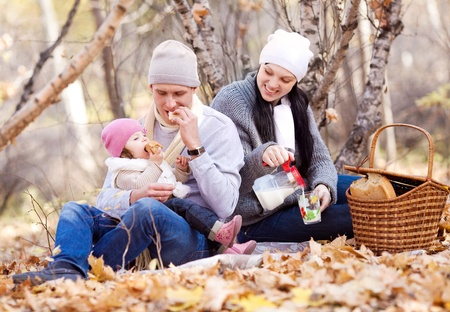 happy young family with their daughter spending time outdoor in the autumn park (focus on the man) Stock Photo - 10944997