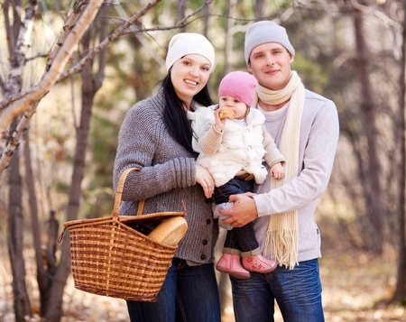 happy young family with their daughter spending time outdoor in the autumn park (focus on the baby) Stock Photo - 10944991