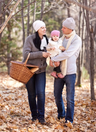 happy young family with their daughter spending time outdoor in the autumn park (focus on the woman) Stock Photo - 10944993