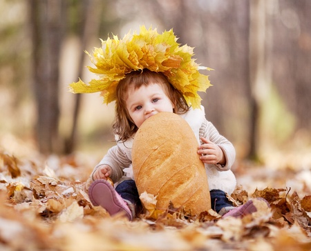 cute baby girl having a picnic, sitting on the gras in the autumn park and eating a long loaf photo