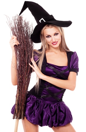 pretty young blond witch with a broom, isolated against white background photo