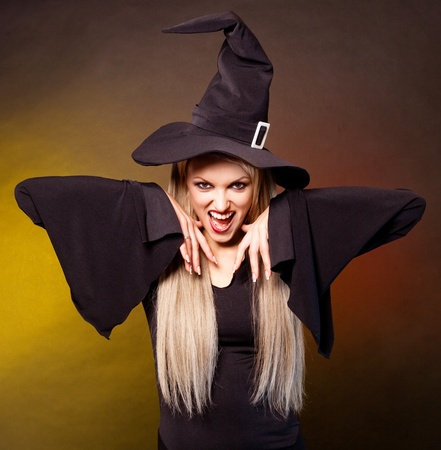 angry young blond witch,against black and yellow studio background photo