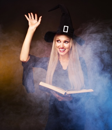 conjuring: blond witch with a book in her hands and clouds of blue smoke around her conjuring, against black and yellow background Stock Photo