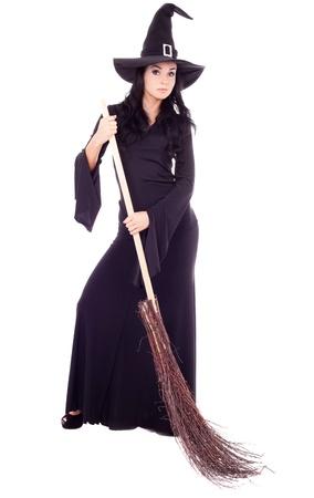brujas sexis: bastante joven bruja morena con una escoba, aislado contra el fondo blanco