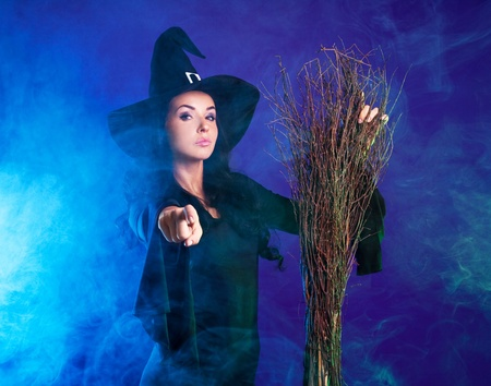 young brunette witch with a broom pointing her finger at us, against purple background photo
