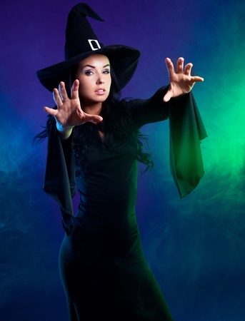 young brunette witch  stretching her hands to us, against purple background photo