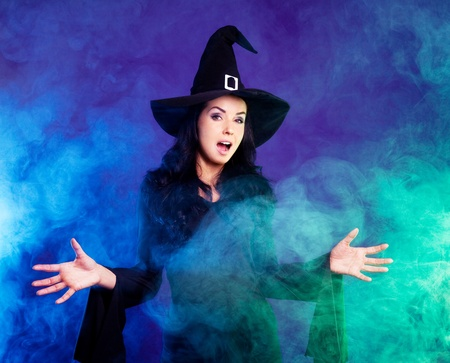spell: young brunette witch  stretching her hands to us, against purple background