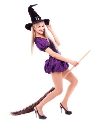 pretty young blond woman dressed as a witch, holding a broom,  isolated against white background photo
