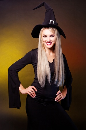 wicked woman: sexy smiling young blond witch, against yellow background