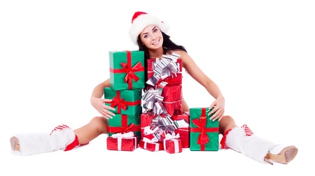 santa helper: beautiful young brunette woman dressed as Santa sitting on the floor with a lot of presents, isolated against white background