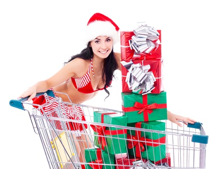 beautiful young brunette woman dressed as Santa with the the shopping cart full of presents, isolated against white background photo