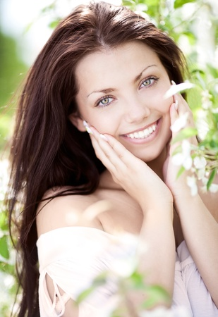 outsides: beautiful young brunette woman near the apple tree on a warm summer day