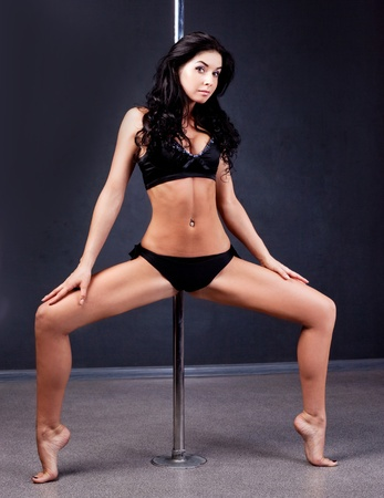 Young sexy pole dance woman against dark background Stock Photo - 11076882