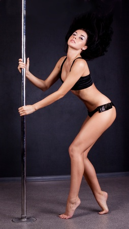 pole dance: Young sexy pole dance woman against dark background