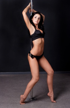 female sexuality: Young sexy pole dance woman against dark background