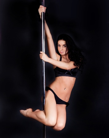 metal pole: Young sexy pole dance woman against dark background