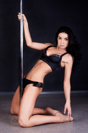 pies descalzos: Joven sexy pole dance mujer contra el fondo oscuro Foto de archivo