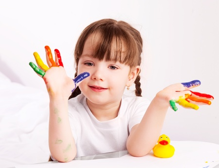 happy cute five year old girl sitting by the table and  painting with watercolor at home Stock Photo - 11076779