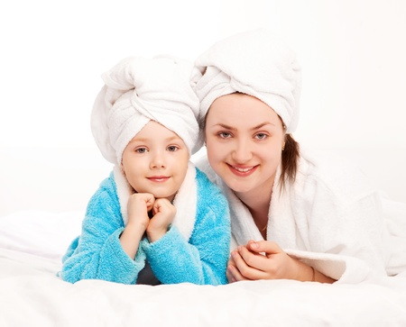 beautiful young mother and her five year old daughter on the bed at home photo