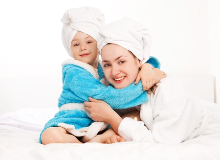 handtcher: sch�ne junge Mutter und ihre f�nf Jahre alte Tochter auf dem Bett zu Hause