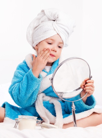 beautiful five year old girl with a mirror applying cream on her face on the bed at home