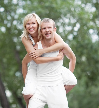 piggyback ride: happy young couple spending time outdoor on a summer day  (focus on the woman) Stock Photo