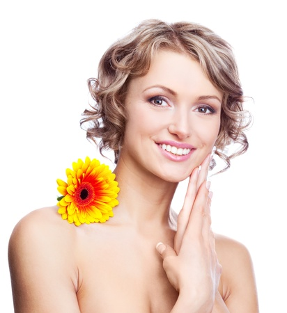 beautiful young blond curly woman with a flower on the shoulder touching her face, isolated against white background photo