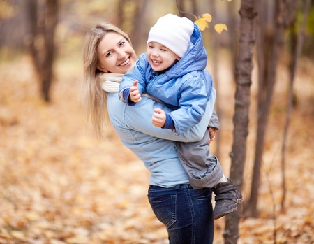 outsides: happy young mother and her son spending time in the autumn park (focus on the woman)