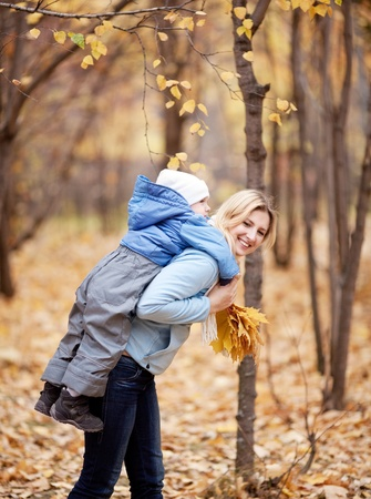 piggyback: happy young mother and her son spending time in the autumn park (focus on the woman)