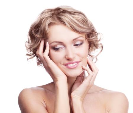 mujer rubia bastante joven con el pelo rizado tocando su mejilla y el pelo y mirando hacia abajo, aislados contra blancos