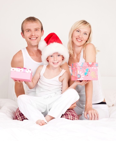 happy family celebrating Christmas: mother ,father and their son on the bed at home  (focus on the child)