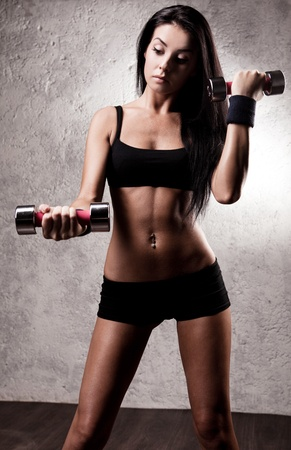 beautiful sexy sporty muscular woman with dumbbells in the gym photo