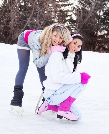 iceskating: two beautiful girls ice skating outdoor on a warm winter day   Stock Photo