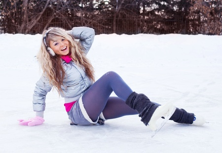 earmuffs: happy beautiful girl wearing warm winter clothes ice skating Stock Photo