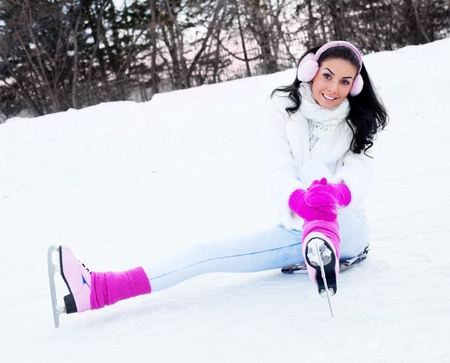 happy beautiful girl wearing warm winter clothes ice skating photo