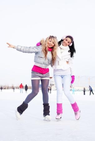 patinaje sobre hielo: dos hermosas chicas de patinaje sobre hielo al aire libre en un d�a caliente del invierno Foto de archivo